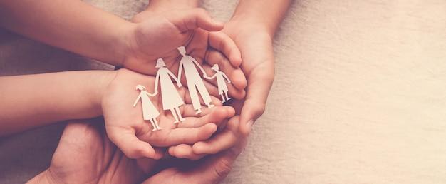 Mani di adulti e bambini che tengono il ritaglio di carta di famiglia, casa di famiglia, affido, sostegno dei senzatetto
