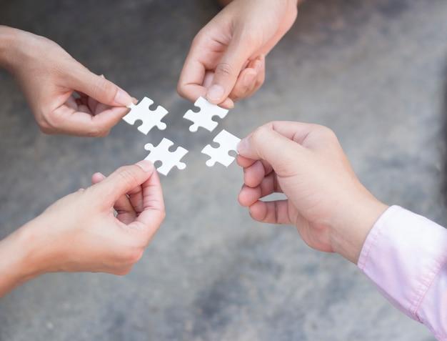 Mani di affari che tengono il concetto di lavoro di squadra di puzzle