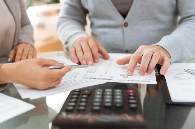 Mani di agente e cliente senior che discutono le informazioni di investimento nel documento finanziario mentre sedendosi al tavolo