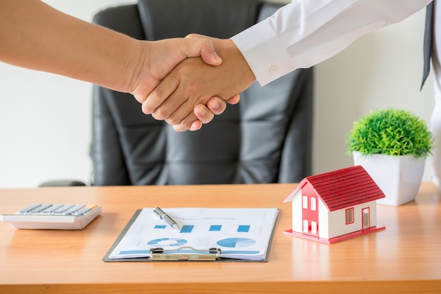 Mani di agente e cliente si stringono la mano dopo il contratto firmato per acquistare un nuovo appartamento.