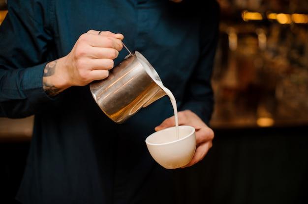 Mani di barista versando del latte in una tazza di caffè