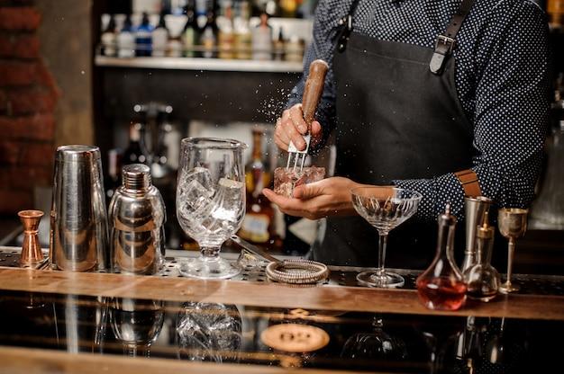 Mani di barman che schiacciano un grosso cubetto di ghiaccio
