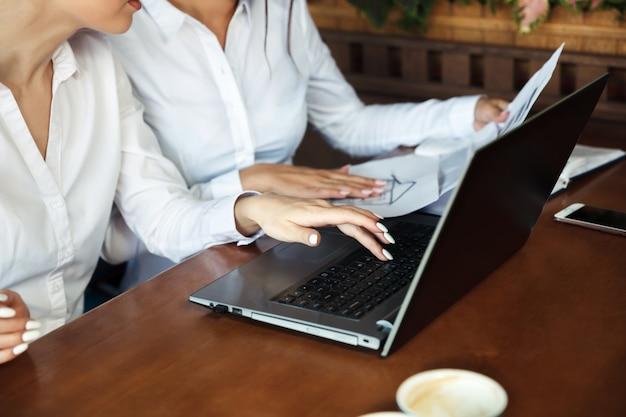 Mani di belle giovani donne di affari che lavorano al computer portatile nel caffè della via all'aperto