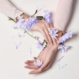 Mani di cura della pelle arte moda e donne fiori blu