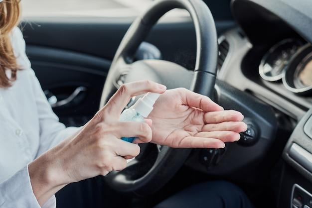 Mani di disinfezione del conducente con spray antibatterico in auto prima di guidare
