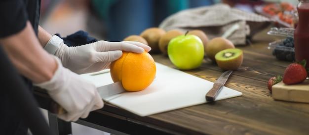 Mani di donna affettare arancia, tagliando gli agrumi.