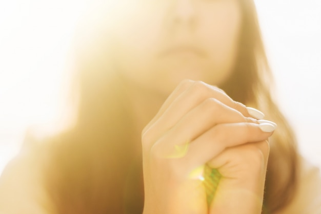 Mani di donna che pregano dio. donna prega per la benedizione di dio di desiderare una vita migliore. implorare perdono e credere nella bontà. preghiera della crisi della vita cristiana a dio