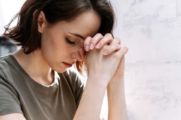 Mani di donna che pregano dio.