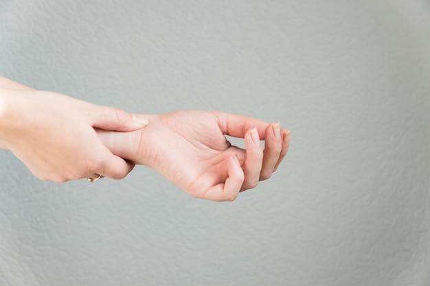 Mani di donna che soffrono di dolore