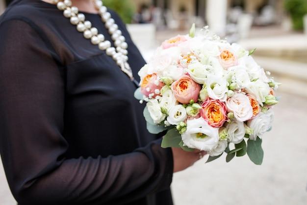 Mani di donna che tengono meraviglioso mazzo di fiori. bellissimo bouquet da sposa e vacanza