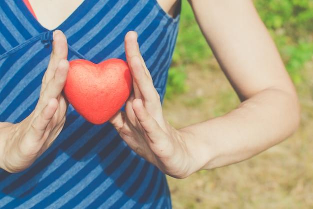 Mani di donna che tiene cuore rosso