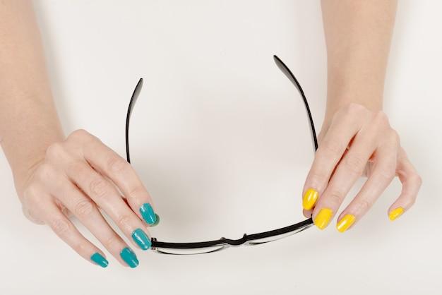 Mani di donna con gli occhiali
