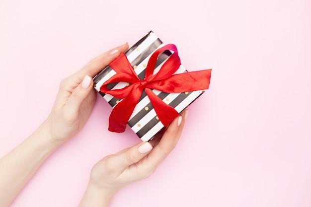 Mani di donna con scatola regalo presente in strisce bianche e nere con un fiocco di nastro rosso isolato sul tavolo rosa vista dall'alto.