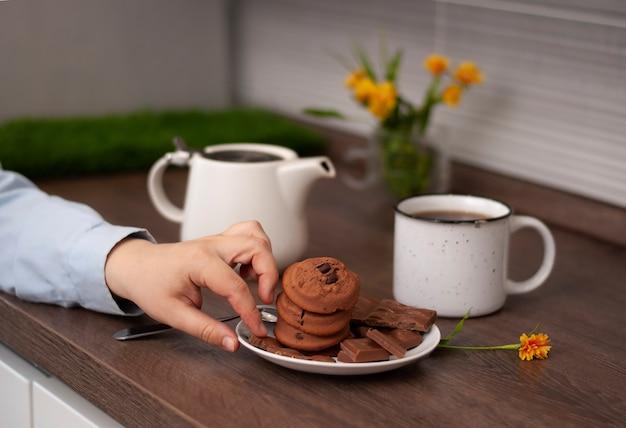 Mani di donna con tazza da tè bollitore bianco e biscotto al cioccolato