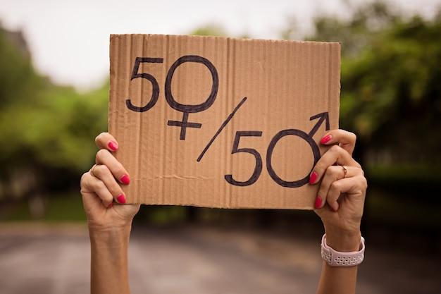 Mani di donna in possesso di un foglio di carta con il simbolo maschile e femminile