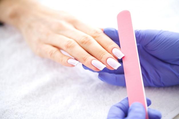 Mani di donna in un salone per unghie che ricevono una procedura di manicure.