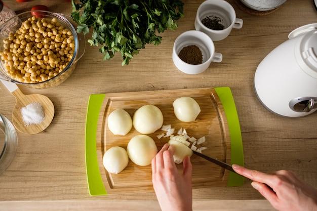 Mani di donna, tagliare le cipolle