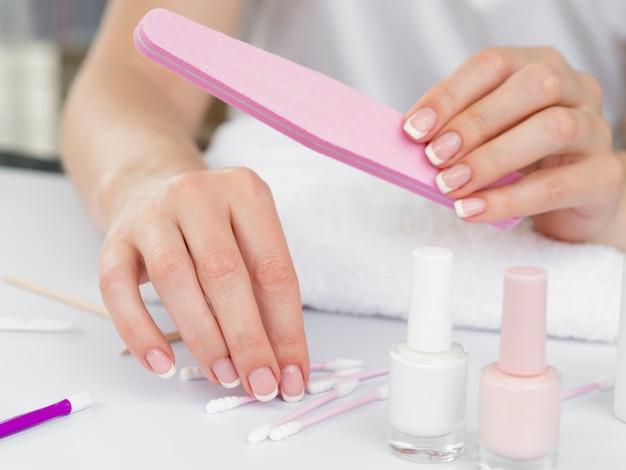 Mani di donna usando strumenti per manicure