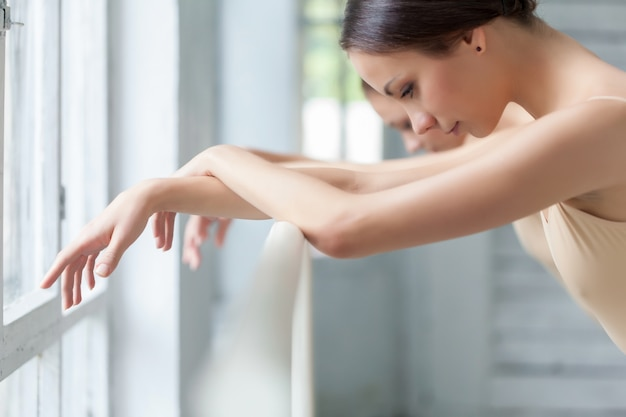 Mani di due ballerini classici alla sbarra