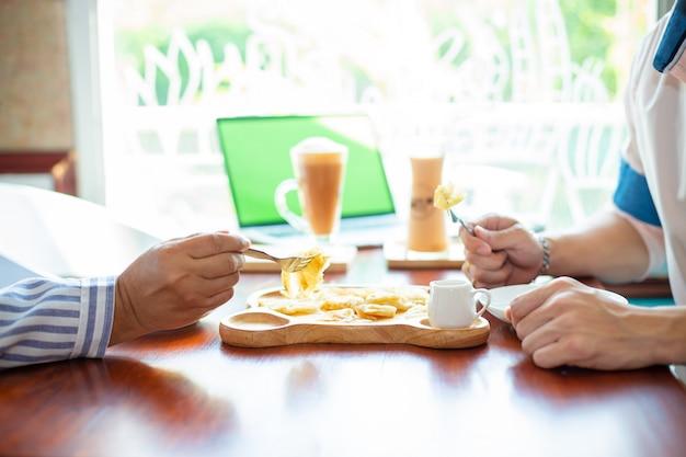 Mani di due persone che mangiano dessert