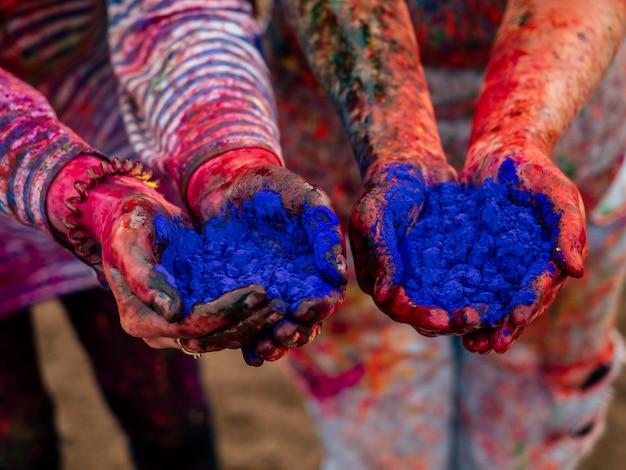 Mani di due ragazze nelle mani della vernice