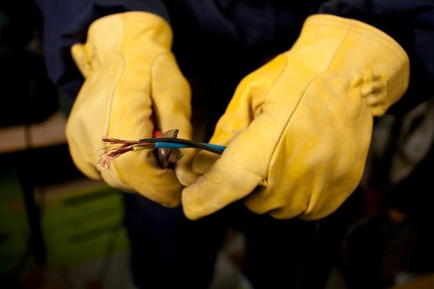 Mani di elettricista con guanti spelatura fili