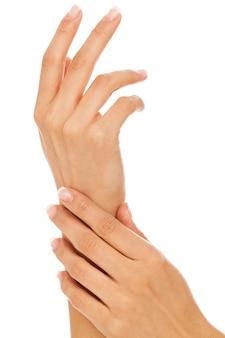 Mani di giovane donna con manicure francese