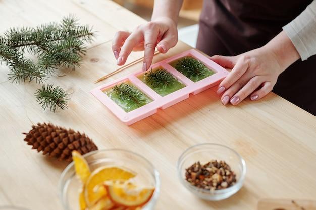 Mani di giovane donna creativa che mette le conifere nella massa di sapone liquido in stampi in silicone mentre si finisce il lavoro creativo