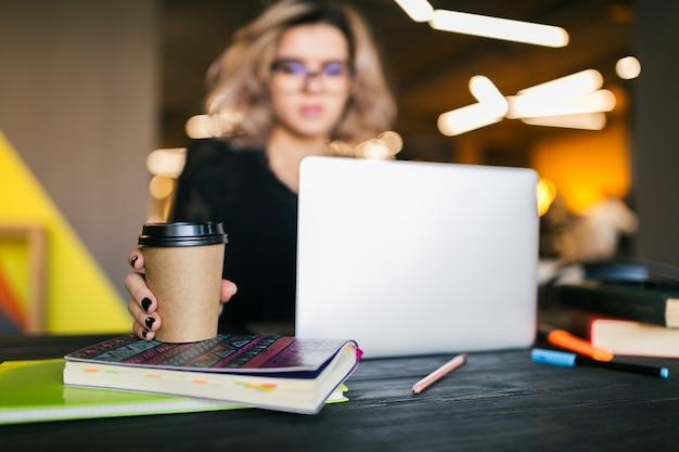 Mani di giovane donna graziosa che si siede al tavolo in camicia nera che lavora al computer portatile in ufficio di lavoro congiunto, libero professionista studente occupato, bere caffè