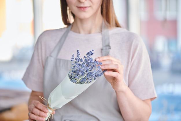 Mani di giovane fiorista femminile che imballano mazzo di lavanda in carta mentre lavorando nello studio