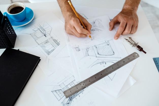 Mani di giovane uomo d'affari che tengono matita e disegno schizzo al tavolo. interno di ufficio moderno bianco