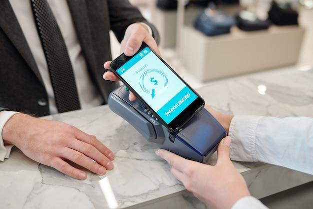 Mani di giovane uomo mobile con smartphone che effettua il pagamento senza contatto per i vestiti che ha comprato in boutique