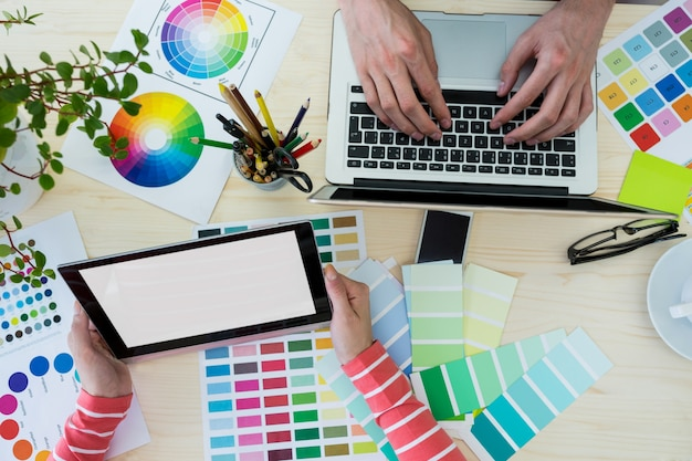Mani di graphic designer con laptop e tablet digitale