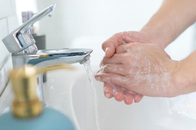 Mani di lavaggio del primo piano nel lavandino