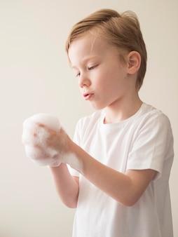 Mani di lavaggio del ragazzo di vista laterale