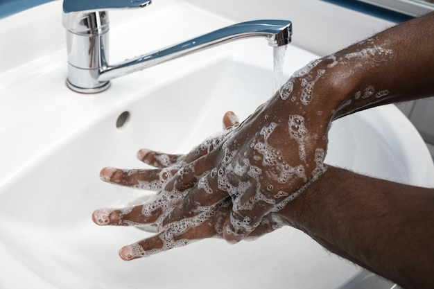 Mani di lavaggio dell'uomo con attenzione nella fine del bagno su. prevenzione dell'infezione e diffusione del virus dell'influenza