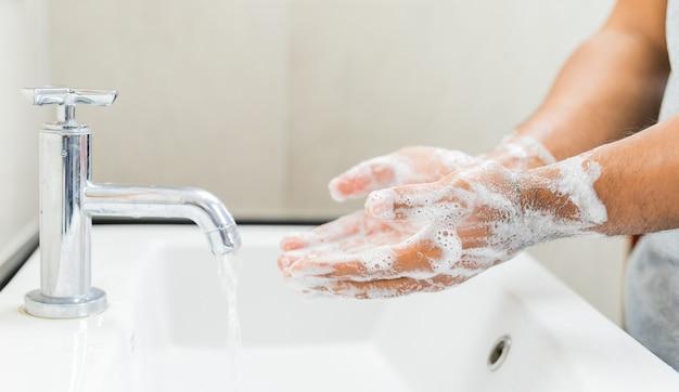 Mani di lavaggio uomo con sapone.