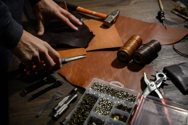 Mani di maestri della pelletteria che tagliano un pezzo di pelle naturale con uno strumento di lavorazione. flusso di lavoro in officina.