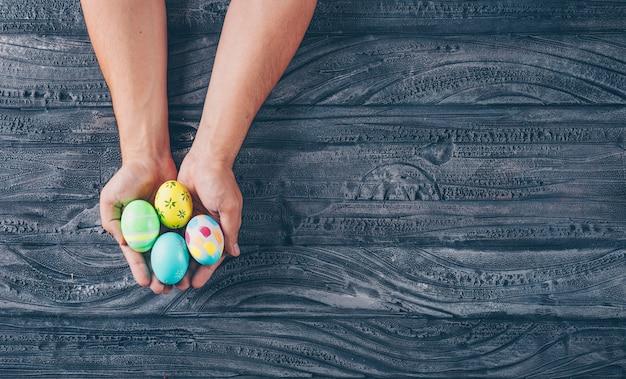 Mani di man_s piene di uova di pasqua su fondo di legno scuro.