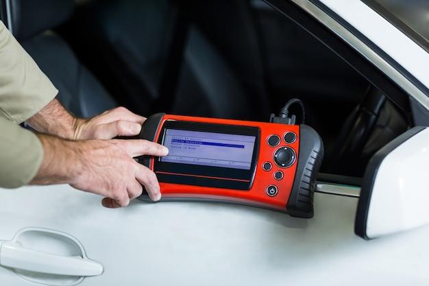 Mani di meccanico utilizzando uno strumento diagnostico