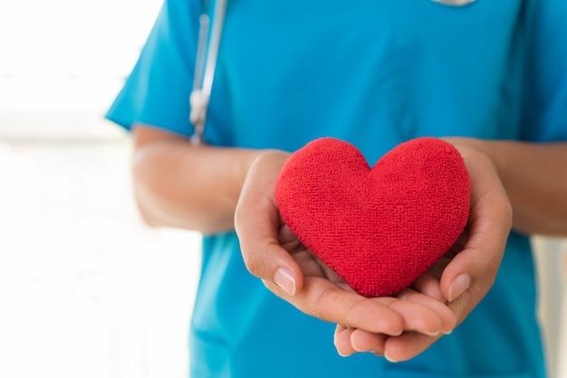 Mani di medico che tengono cuore rosso