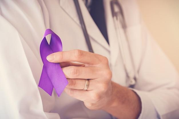 Mani di medico che tengono nastro viola, malattia di alzheimer, consapevolezza dell'epilessia