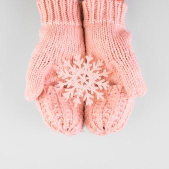 Mani di persona in muffole con fiocco di neve di carta