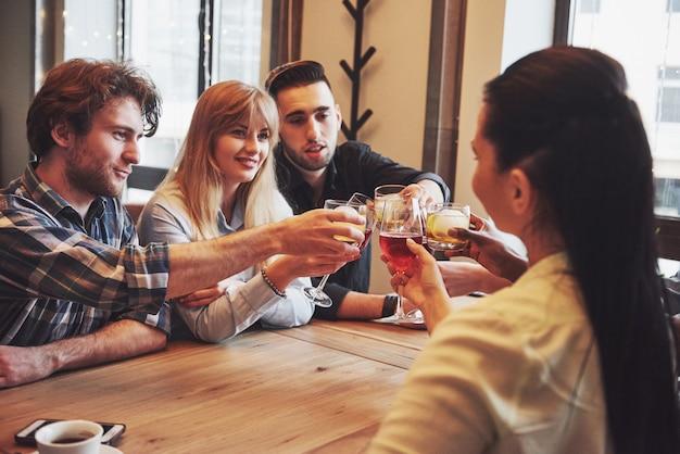 Mani di persone con bicchieri di whisky o di vino, celebrando e brindando in onore del matrimonio o altra celebrazione