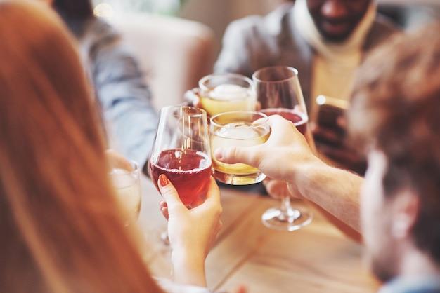 Mani di persone con bicchieri di whisky o vino, celebrando e brindando