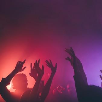 Mani di persone in discoteca