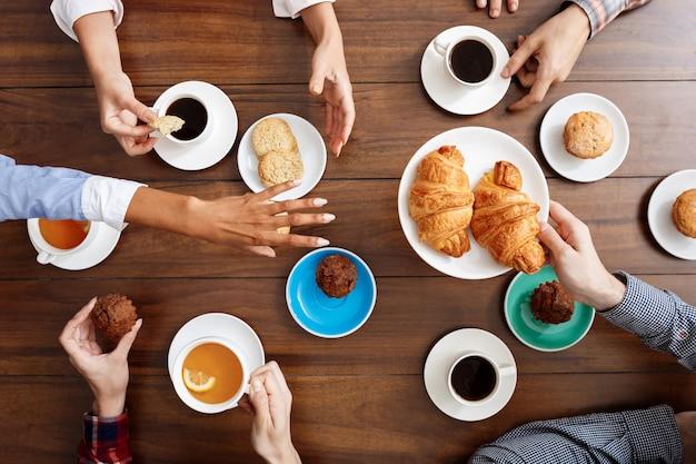 Mani di persone sul tavolo di legno con cornetti e caffè.
