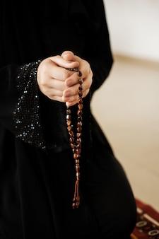 Mani di preghiera di una donna che tiene un rosario
