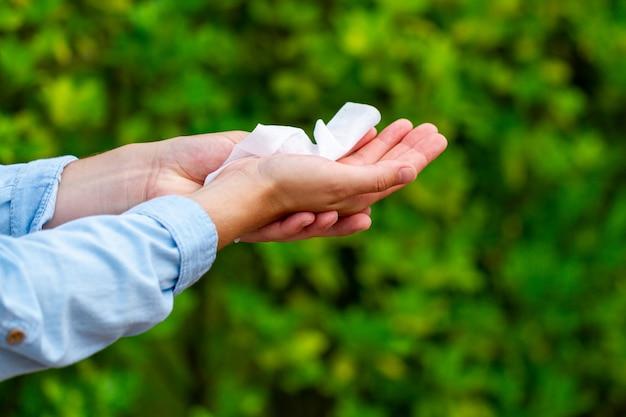 Mani di pulizia con salviettine umidificate nel parco