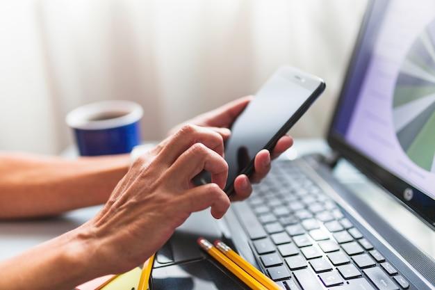 Mani di raccolto che passano in rassegna smartphone in ufficio